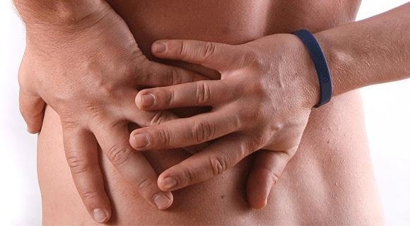 мужчина держится руками за поясницу слева от боли